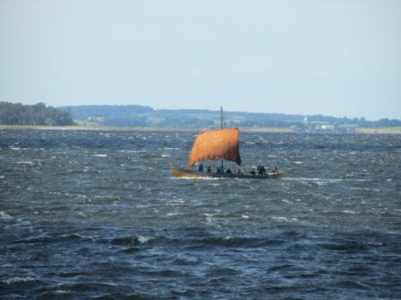 Reconstructed Viking ship sailing in the Roskilde fiord with a woollen sail.