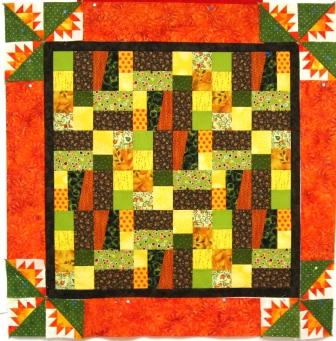 The quilt on the design wall, with the second orange border, including the Kansas Troubles blocks, pinned into place.