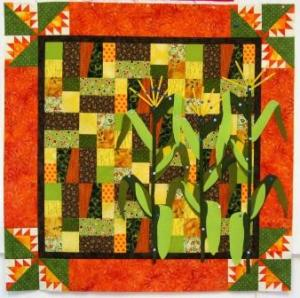 The quilt top with the reconstructed corn stalks pinned on.